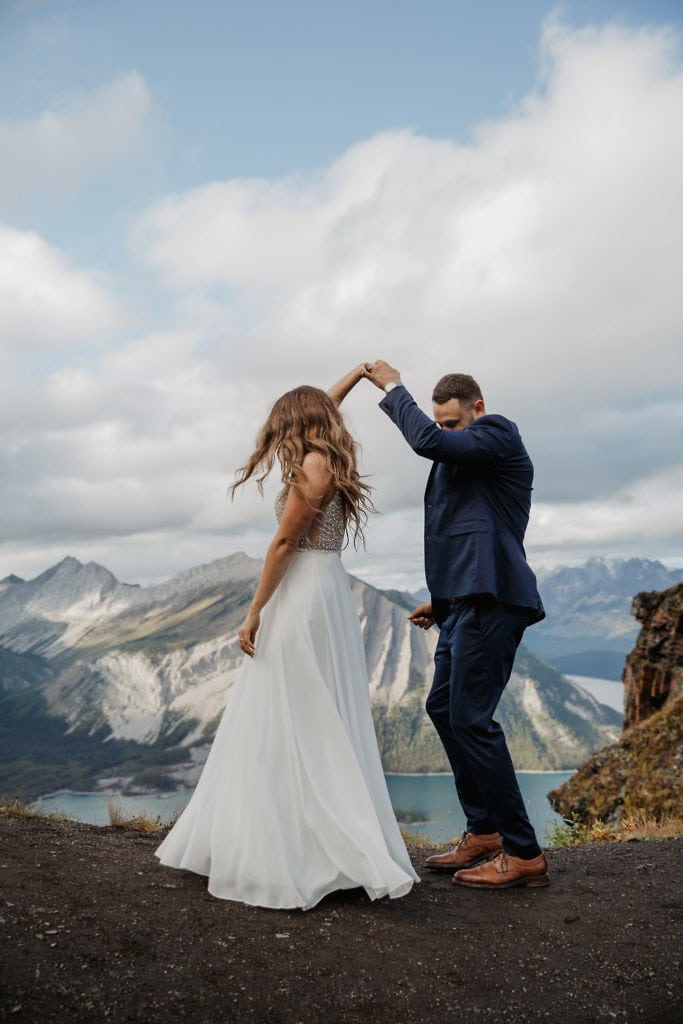 A couple getting married on top of a mountain having their first dance.