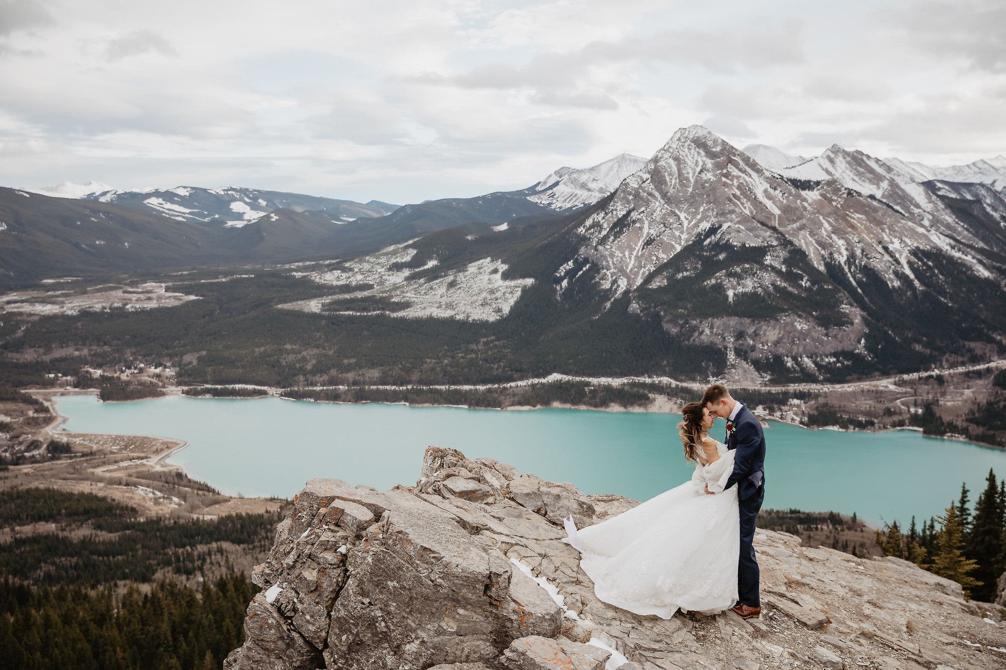A couple on their mountain hiking elopement in Kananaskis, Alberta, Canadian Rockies. Captured by Banff wedding and elopement photographers. The couples are standing on the edge of a cliff surrounded by mountain range with turquoise coloured alpine lake behind them on a windy sunny day.