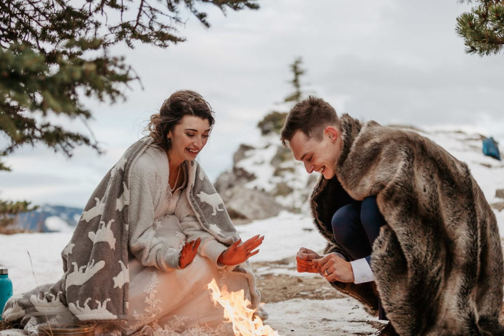 Bride and groom are sitting by a portable campfire on their hiking wedding in Kananaskis mountains. They are having fun warming their hands.