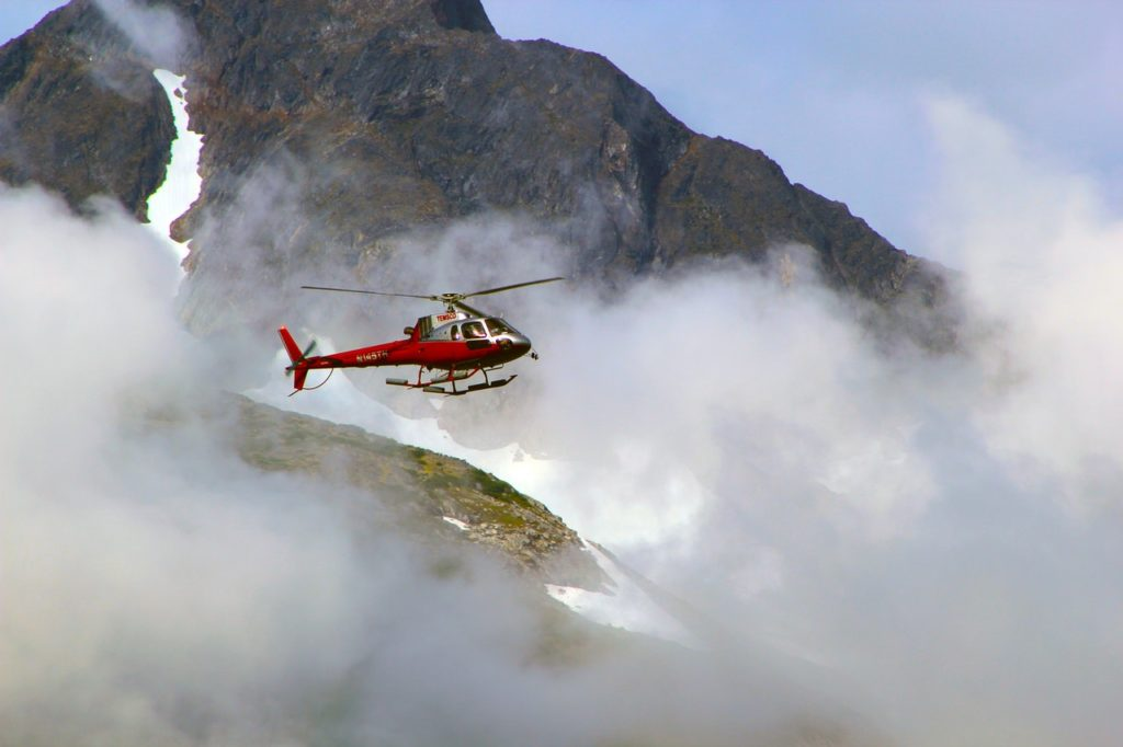 A helicopter flying through the mountain range during misty weather for a mountain top helicopter elopement in Banff