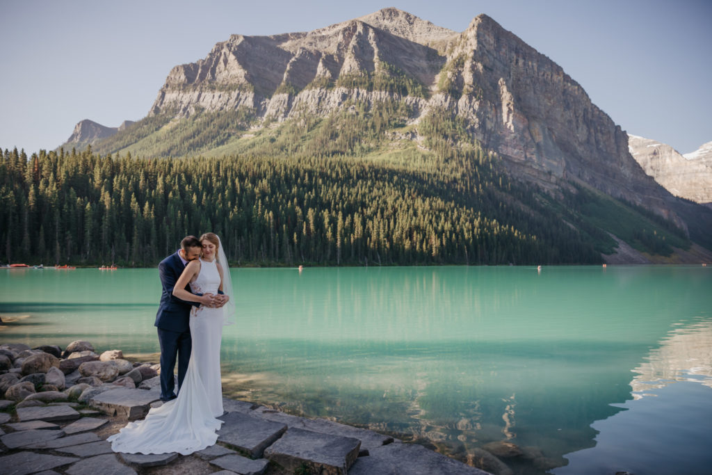A couple standing in front of a turquoise colour lake, Lake Louise on their elopement day in Banff with the mountain range behind them.