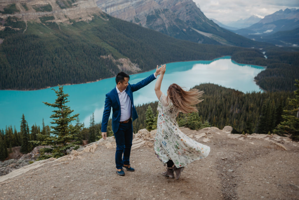 A couple getting married by the blue turquoise colour lake at Peyto Lake in Banff. They are dancing at sunrise.