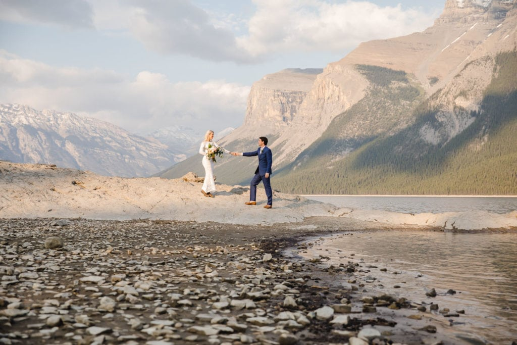 A couple are eloping by the lake called Lake Minnewanka and surrounded by mountain range in Banff National Park