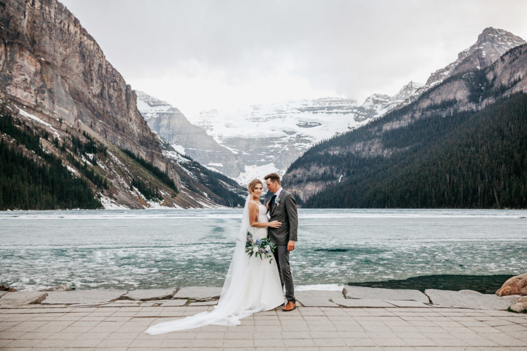 Bride and Groom standing in front of frozen Lake Louise on their winter elopement day in Banff