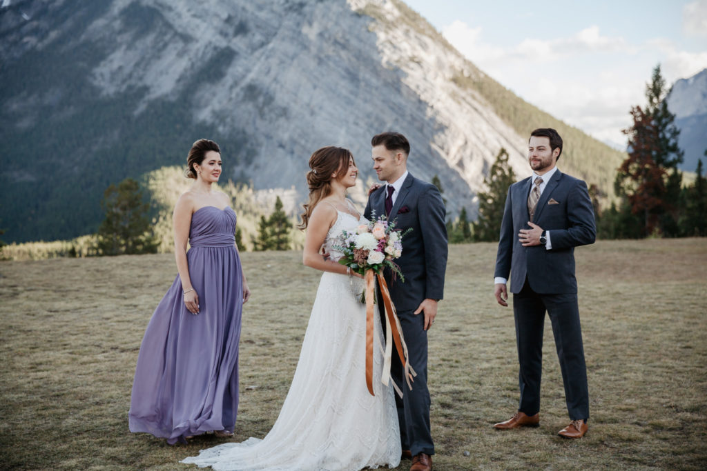 Bride and Groom are eloping in Banff at Tunnel Mountain Reservoir with close family and friends. They are surrounded by mountains as the sun is setting.