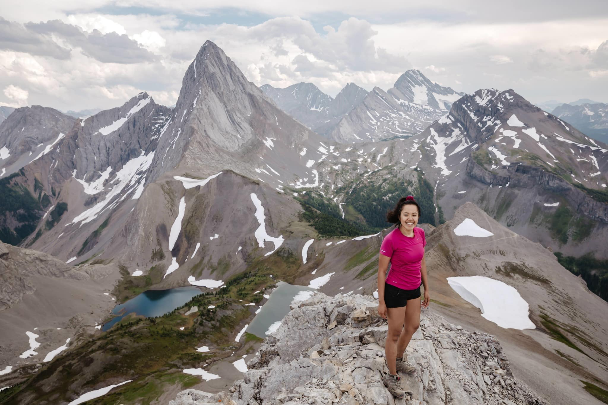 A female Canmore wedding photographer standing on top of a mountain near