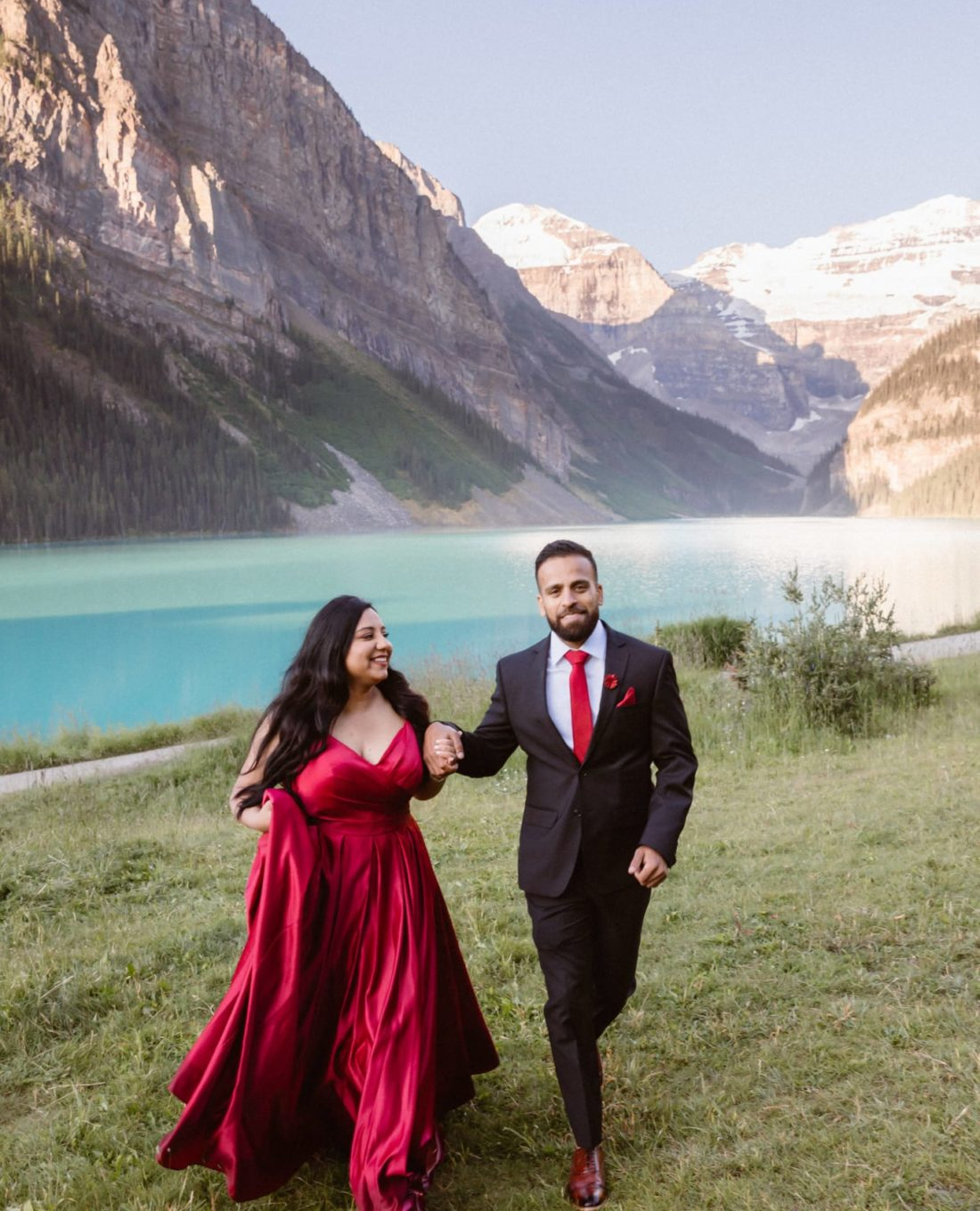 An engaged couple running together at Lake Louise. She is wearing a a red dress and he is wearing a suit with red tie