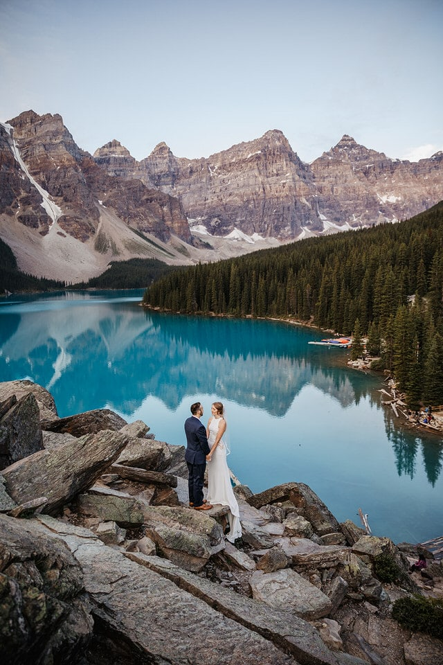 Bride and groom holding hands and looking at each other while standing by the turquoise blue alpine lake and surrounded by mountains in Banff National Park