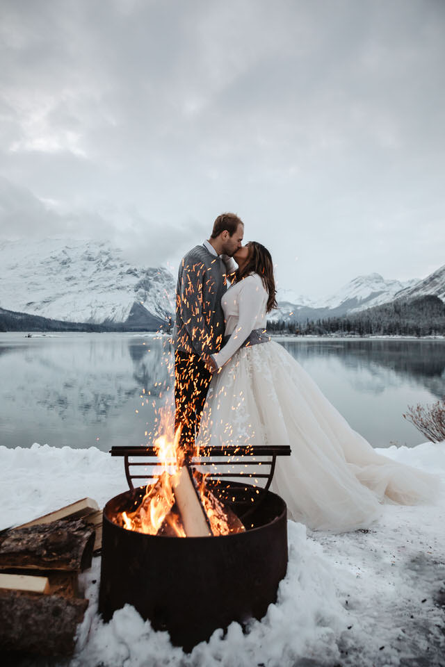 Bride and groom dancing outdoor beside a campfire and by a lake on their winter wedding surrounded mountains