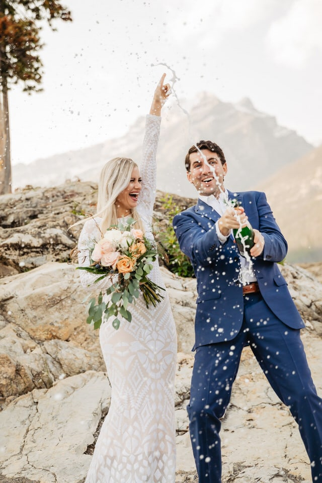 Groom popping champagne and blond haired bride cheering beside him on their wedding day surrounded by mountains